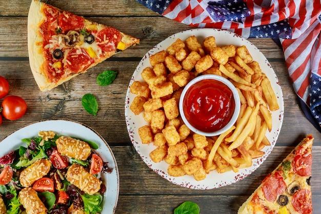 Table de fête festive avec pommes de terre frites, pizza et légumes pour les vacances américaines.
