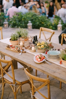 Une table de fête avec des fleurs fraîches dans des pots et des citrons dans une assiette creuse dans un restaurant avec des chaises et des invités
