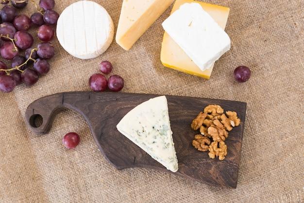 Table de fête de fromage, apéritif de vacances parfait avec écrou sur planche de bois rustique.