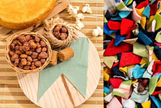 Table de fête de juin fête typiquement brésilienne de juin. gâteau, cacahuètes, pop-corn et pignons de pin. fond coloré