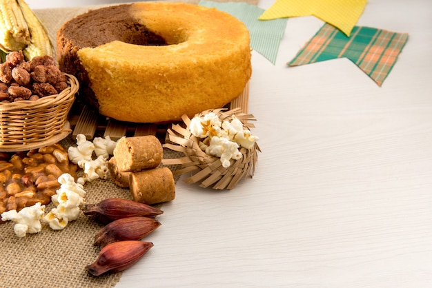 Table de fête de juin. fête typiquement brésilienne de juin. gâteau, maïs, arachides, maïs soufflé et pignons de pin.