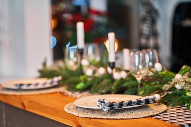 La table de fête de noël est décorée de branches d'arbre de noël, de bougies et de guirlandes