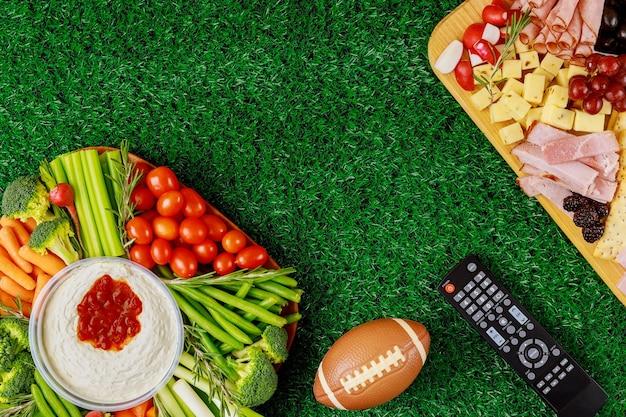 Table de fête avec nourriture et boisson pour regarder le match de football américain.
