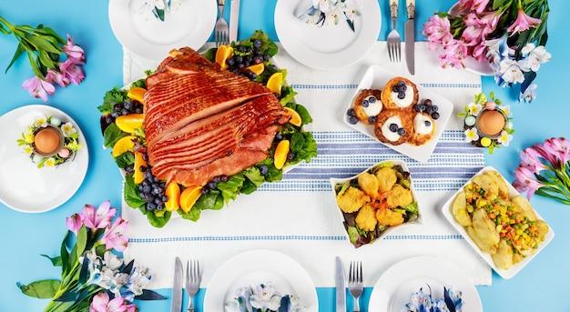 Table de fête de pâques avec jambon, salade et crêpes. dîner de pâques.