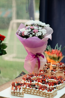 Table de fête pour le dix-huitième anniversaire avec un gâteau et un bouquet de belles fleurs