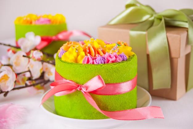 Table de fête de printemps pâques. petit gâteau vert aux fleurs de crème au beurre, branche de fleur de cerisier et coffret cadeau