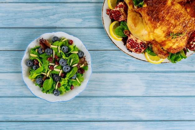 Table de fête avec salade de printemps et poulet entier pour les vacances