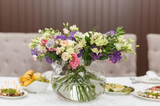 Table de fête servie avec bouquet de roses sauvages dans un vase