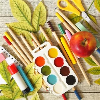 Table avec feuilles d'automne pomme et fournitures scolaires vue de dessus à plat