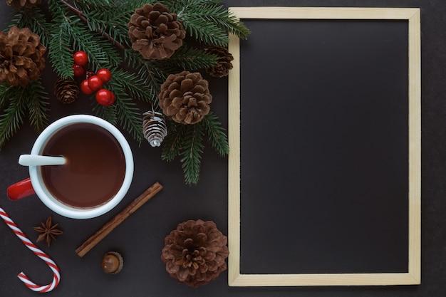 Table en granit noir décorer avec tableau noir ou tableau noir, feuille de pin et cônes et tasse de chocolat dans le concept de noël