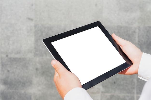 Table de gros plan avec un écran blanc entre les mains d'un homme d'affaires par un mur de béton.