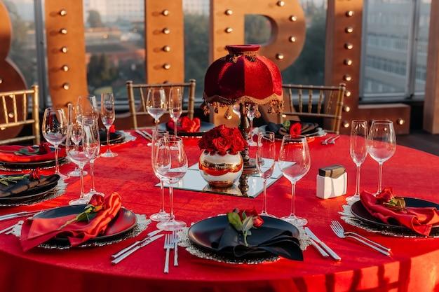 Table d'hôtes de style noir rouge et or nappe de décoration élégante couverts de roses fraîches