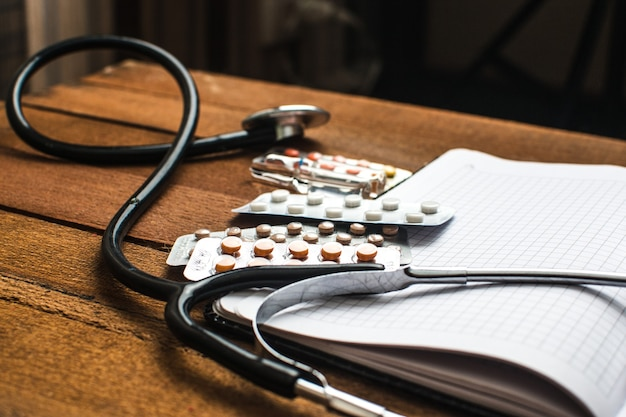 Sur la table, il y a des ampoules, à côté de différentes pilules, médicaments et médicaments