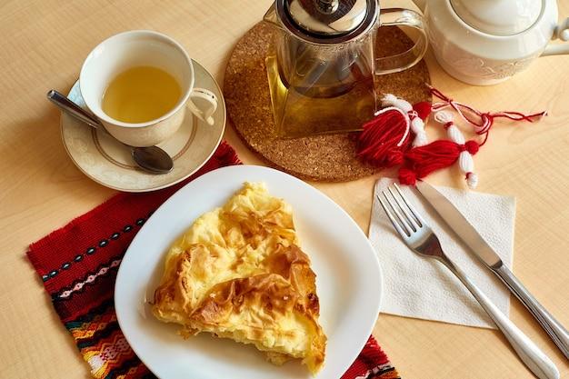 Sur la table il y a une omelette, une fourchette, un couteau, une théière avec du thé, un sucrier, une tasse et une soucoupe dans une assiette