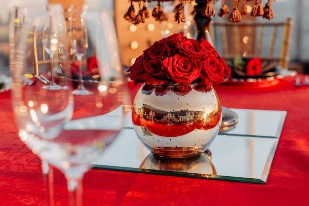 Table d'invités pour banquet en vase décor de style noir rouge et or avec roses sur miroir