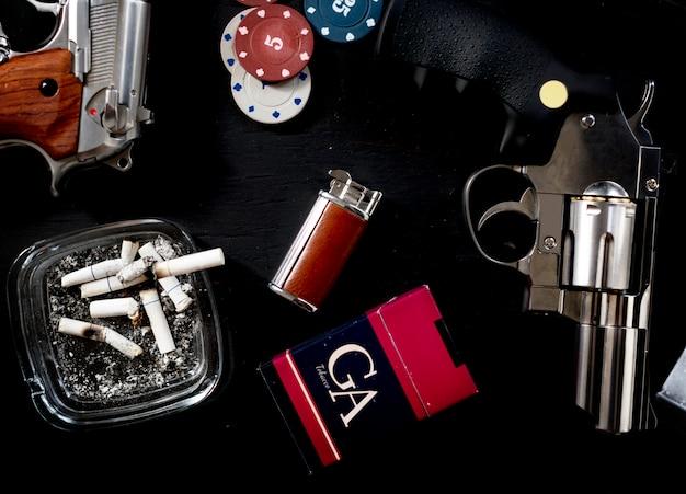 Table de jeu et de gangster mise en place avec des cigarettes et des armes à feu.