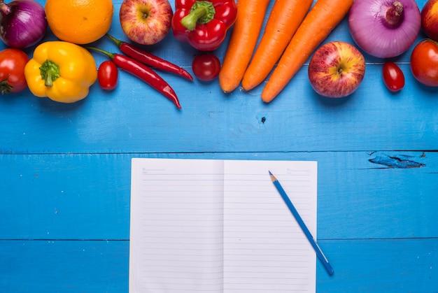 Table avec des légumes et un bloc-notes