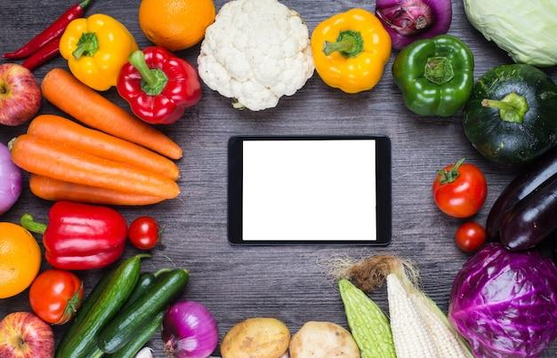 Table avec des légumes et une tablette