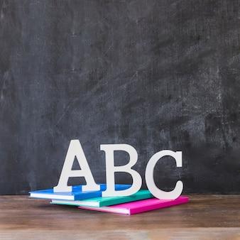 Table avec des lettres de l'alphabet sur les livres près du tableau noir