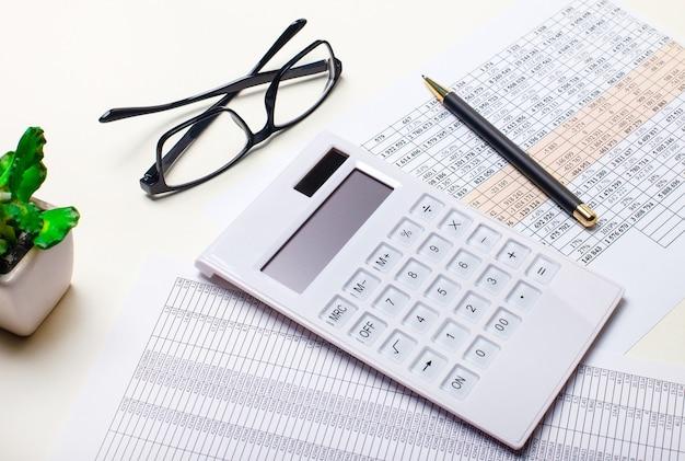 Sur une table lumineuse, il y a une plante en pot, une calculatrice blanche, des lunettes à monture noire, des papiers et un stylo. gros plan sur le lieu de travail. concept d'entreprise