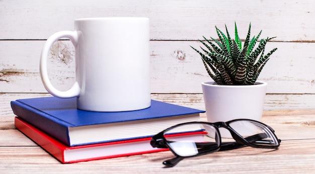Sur une table lumineuse se trouvent des agendas, une plante en pot, des verres à monture noire et une tasse blanche avec un espace pour insérer du texte.
