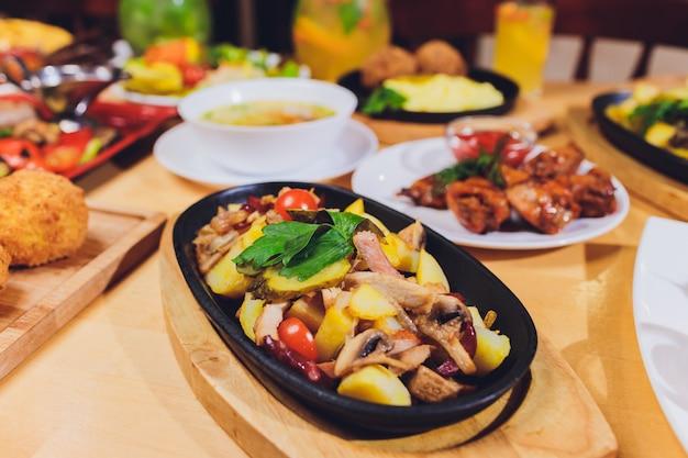 Table à manger avec une variété de collations et de salades. saumon, olives, vin, légumes, pain grillé au poisson. le concept d'un dîner de fête en famille.