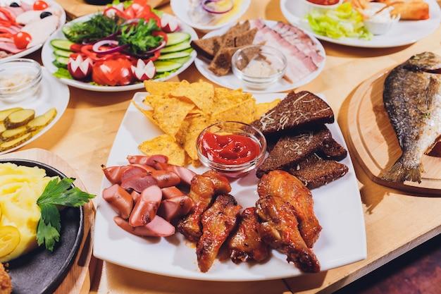 Table à manger avec une variété de collations et de salades. saumon, olives, vin, légumes, pain grillé au poisson.