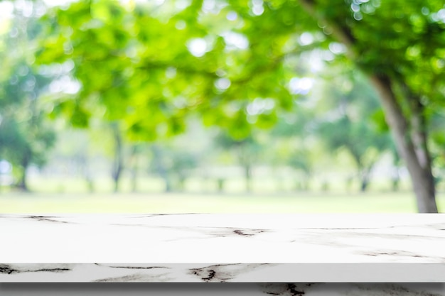 Table de marbre blanc vide sur fond de parc vert flou, montage de l'affichage du produit