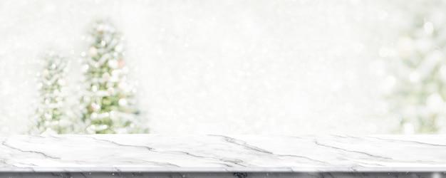 Table en marbre avec flou de lumière de chaîne d'arbre de noël flou fond avec neige