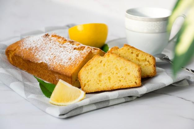 Table en marbre avec gâteau à l'orange fraîchement cuit au four sur une serviette de cuisine, agrumes, tasse et plante d'intérieur