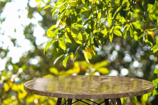 Table en marbre vide dans la cour avec des arbres verts