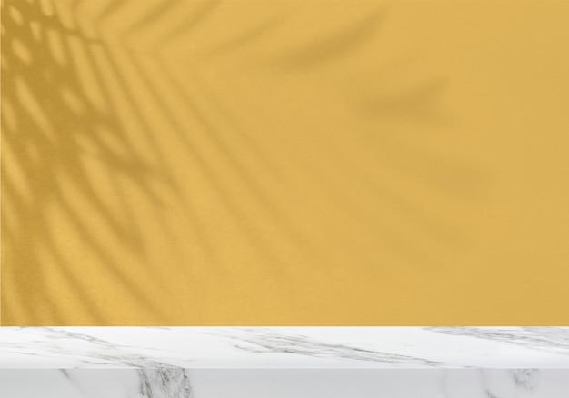 Table en marbre vide avec ombre de feuilles sur fond de produit mural texturé jaune