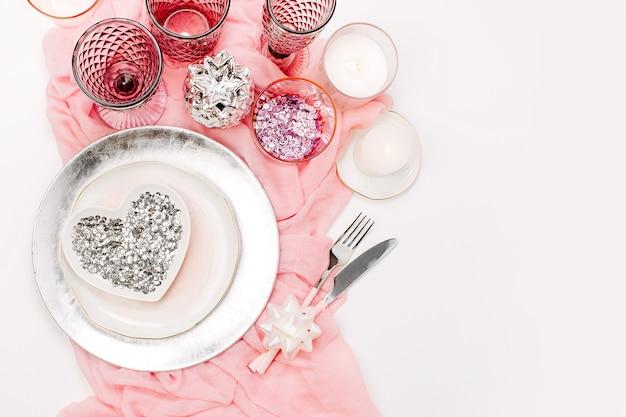 Table de mariage ou de fête. assiettes, verres à vin, bougies et couverts avec textile décoratif sur fond blanc. bel arrangement sur la couleur rose