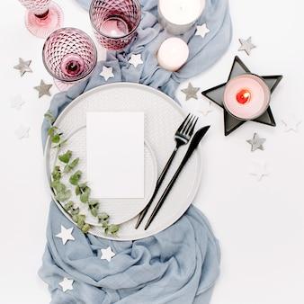 Table de mariage ou de fête. assiettes, verres à vin, bougies et couverts avec textile décoratif gris sur fond blanc. belle disposition.