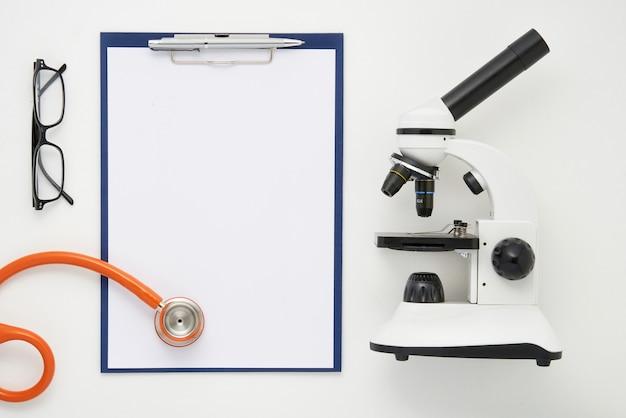 Table de médecin avec microscope, stéthoscope et verres, vue de dessus