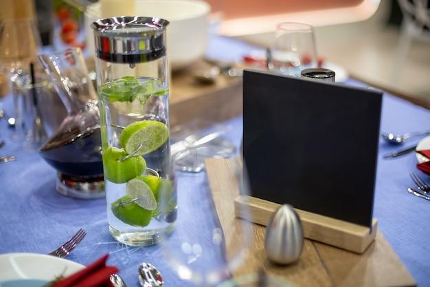 Une table avec une nappe bleue est servie de manière festive, il y a des appareils en acier et une salière, une assiette blanche et nue avec une serviette rouge, une carafe remplie d'eau de chaux et une assiette noire pour copier