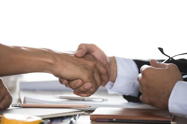 Table de négociation, deux hommes d'affaires prospères se serrent la main comme un accord.
