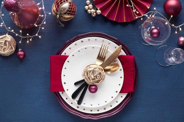 Table de noël avec assiette blanche, ustensiles dorés, décor rouge foncé et doré. mise à plat, vue de dessus sur table textile en lin bleu foncé. guirlande de lumières de noël.
