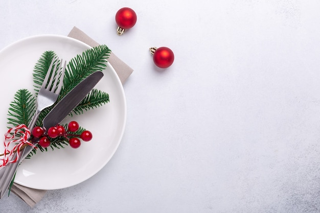 Table de noël avec assiette blanche vide, cannes de bonbon, branche de sapin et couverts avec décorations festives sur fond de pierre - image