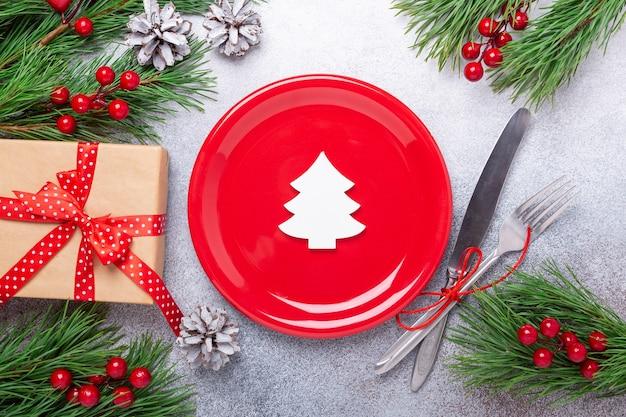 Table de noël avec assiette rouge vide, couverts avec décorations de fête