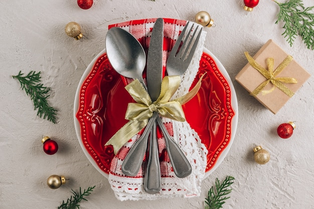 Table de noël avec assiette rouge vide, couverts sur serviette