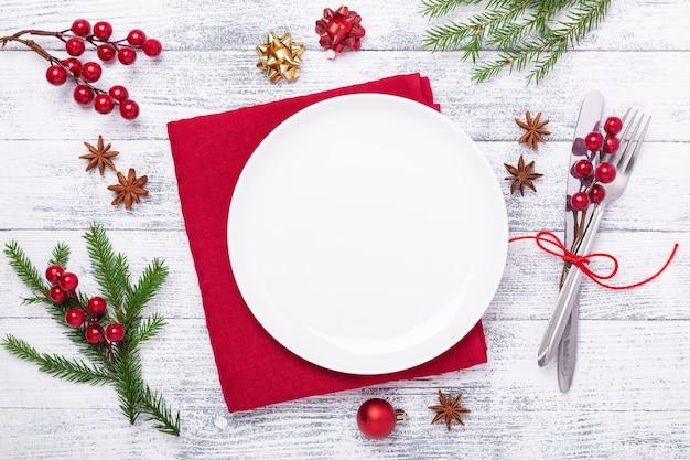 Table de noël avec couverts en assiette blanche vide avec des décorations de fête