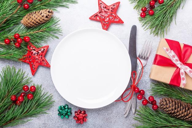 Table de noël avec couverts de boîte cadeau plaque blanche vide avec des décorations de fête