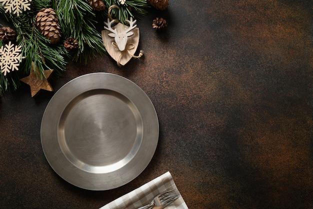 Table de noël avec décoration naturelle et assiette sur brown