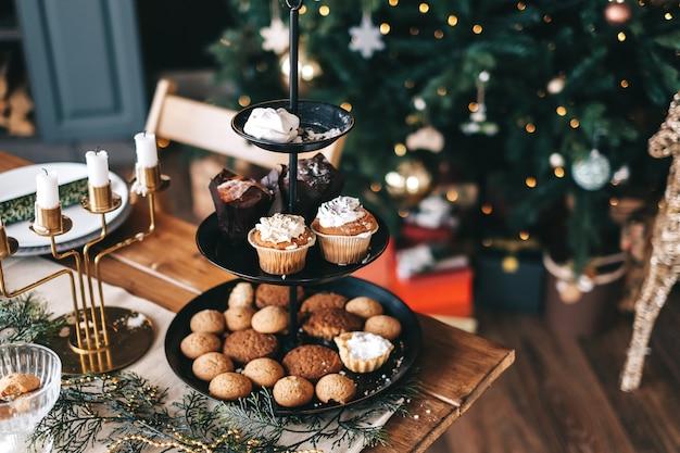 Table de noël festive avec des biscuits sucrés et des gâteaux dans la cuisine avec des décorations.