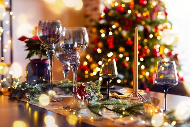 Table de noël joliment décorée sur l'arbre de noël défocalisé et les lumières