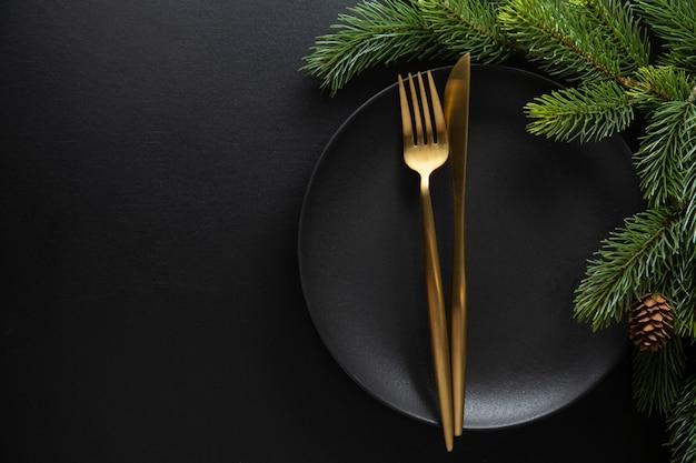 Table de noël servie dans des tons sombres avec une déco dorée.