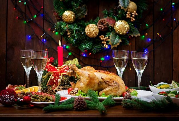 Table de noël servie avec une dinde, décorée de guirlandes lumineuses et de bougies