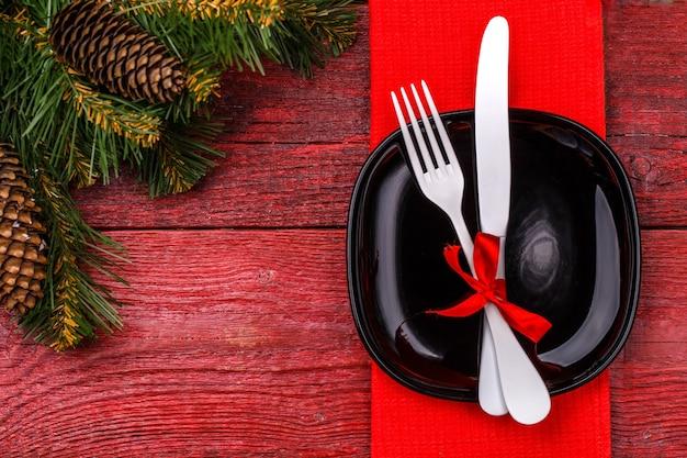 Table de noël avec serviette rouge, assiette noire, fourchette et couteau blancs, arc rouge décoré et branches de pin de noël. table de vacances de noël.