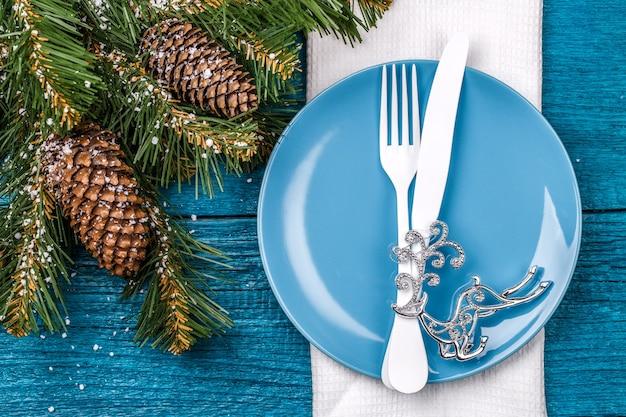 Table de noël - table bleue avec serviette blanche, assiette bleue, fourchette et couteau blancs, jouet d'arbre de noël décoré - cerf argenté et branches de pin de noël. fond de vacances de noël.